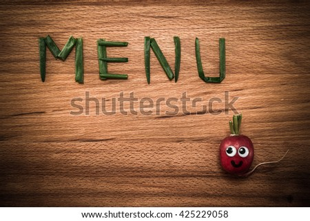 Mr. Radish is smiling and looking at the onion petals folded in the form of the word 'MENU' on wooden table. Close-up view from above, image vignetting and the hard tones - stock photo