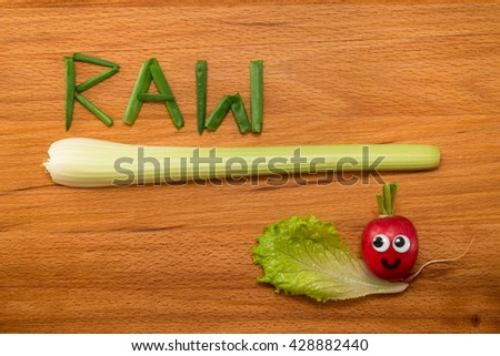 Mr. Radish is smiling and looking at the onion petals folded in the form of the word 'RAW' and celery on wooden table. Close-up view from above - stock photo
