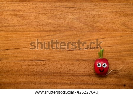 Mr. Radish is smiling on wooden table. Close-up view from above - stock photo