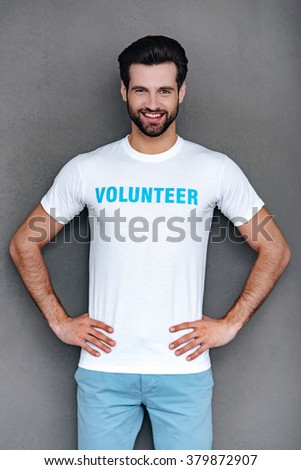 Mr. Volunteer. Confident young man in volunteer t-shirt keeping hands on hips and looking at camera with smile while standing against grey background