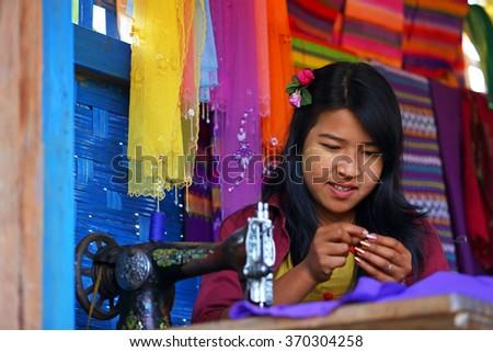 MRAUK U, MYANMAR - JAN 17: Unidentified Burmese woman sewing machine working in his village and  on January 17, 2016 in Mrauk U, Myanmar. - stock photo