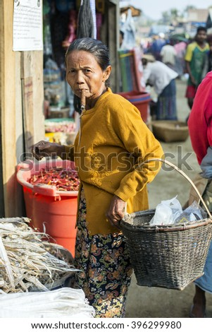MRAUK U, MYANMAR - JANUARY 30, 2016: An unidentified Burmese woman smokes a hand rolled cigar while shopping at the local market.