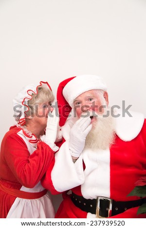 Mrs Claus whispers a secret into Santa's ear. - stock photo