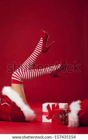 Mrs santa claus legs in striped stockings with christmas gifts  - stock photo