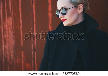 Ms. Leon Killer concept. Portrait of young beautiful girl in trendy black coat and glasses posing over old rusty wall. Perfect skin and make-up. Glazed hair. Vogue style. Outdoor shot