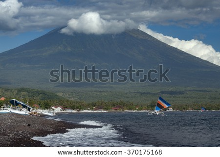 Mt. Agung, Bali, Indonesia. The volcano, Gunung Agung, which last erupted in 1963 looms large over the small fishing village in the Amed area of Bali Indonesia. Fishing boats return in the morning. - stock photo