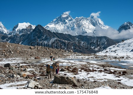 Mt.Everest and a group of porters at Renjo mountain pass, Nepal