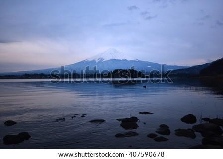 Mt. Fuji at dawn with peaceful lake reflection - stock photo