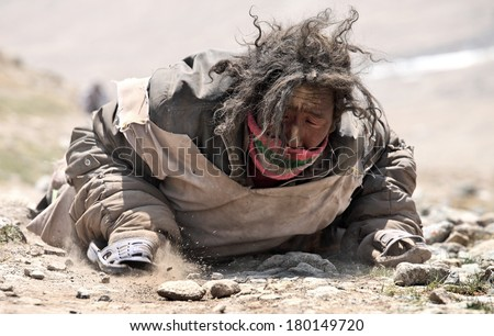 Mt Kailash, Tibet, China - May 26, 2012: Buddhist pilgrim making the kora (circumambulation) around Mt. Kailash and performing full body prostrations - stock photo