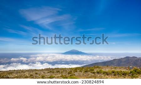 Mt.Meru rises above the morning clouds, Machame-Mweka Route, Kilimanjaro National Park, near Arusha, Tanzania, Africa - stock photo