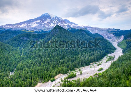 Mt. Rainier Cascade Range Volcano. Nisqually and Wilson Glaciers visible.Looking down into a valley created by the receeding glacier that also creates the river flowing along the bottom. - stock photo