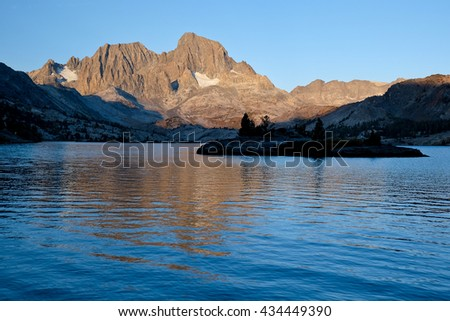Mt Ritter and Banner Peak Tower Over An Alpine Lake and Small Island.  Garnett Lake, The Ansel Adams Wilderness, Sierra Nevada, California - stock photo