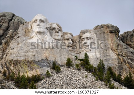 Mt. Rushmore National Memorial Park in South Dakota with neutral sky in background. Sculptures of former U.S. presidents; George Washington,Thomas Jefferson,Theodore Roosevelt and Abraham Lincoln.