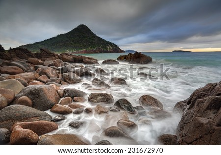 Mt Tomaree is lush covered volcanic rock that rises above sea level The walk to the summit is steep but worth the 360 views.   Taken from the southern end of Zenith Beach. - stock photo