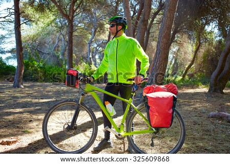 MTB Biker Bicycle touring in a pine forest with pannier racks and saddlebag
