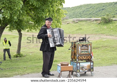 MTSKHETA, GEORGIA - MAY 9: Unidentified street musician plays the accordion near the ancient Djvari Church in Mtsketa, Georgia on May 9, 2014. He is genius and can play the barrel organ (right) also. - stock photo