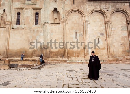 MTSKHETA, GEORGIA - OCT 14: Christian priest standing near the ornamental stone wall of Svetitskhoveli Cathedral, built in 4th century on October 14, 2016. UNESCO World Heritage Site.