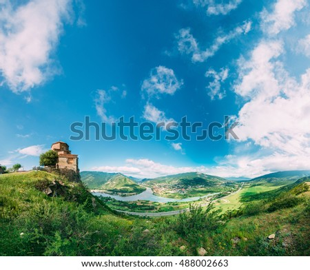 Mtskheta, Georgia. The Ancient Georgian Orthodox Church Of Holly Cross, Jvari Monastery With Remains Of Stone Wall, World Heritage. Scenic Blue Cloudy Sky Background. Panorama