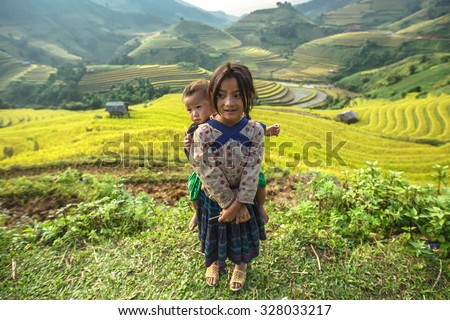 Mu cang chai, VIETNAM September 25 2014 :Children working in rice terrace on 25 /09/2014 in Sapa,Vietnam. Many children in Vietnam are withdrawn from school to be bread-winners for their families