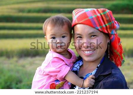 Mu Cang Chai - Yen Bai - Vietnam, September 28, 2014: A Hmong ethnic woman carrying a child in the rice fields