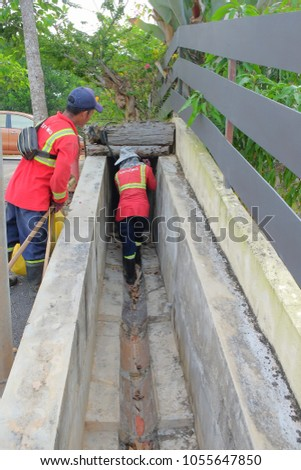 "Muadzam Shah, Malaysia - March 22nd, 2018: Municipal workers ""Alam Flora"" uses sweepers and shovels to clean the garbage in the drain and put into the garbage bag."