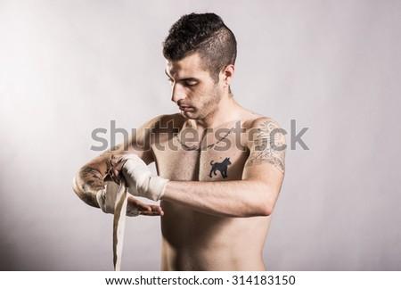 Muai thai fighter posing in studio shot with tattoos - stock photo