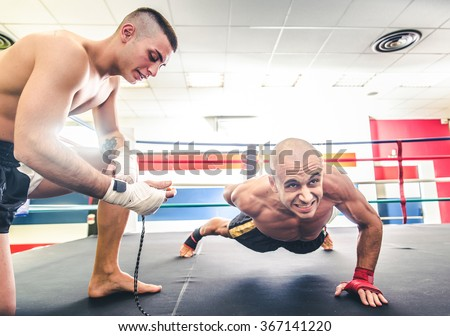 Muay thai fighter doing push ups  - Coach training his athlete for a boxe match - Sportive men working out in a martial arts gym - stock photo