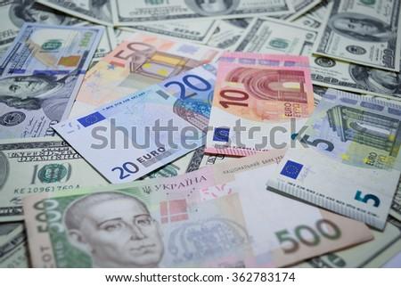 Much money. Many banknotes. Dollar, euro, hryvnia - stock photo