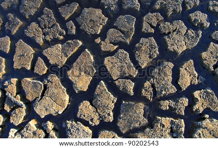 Mud crack texture with water seeping through the cracks - stock photo