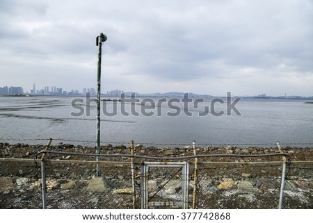 Mud flat, barbed-wire fence in the cloudy day of Oido, Korea - stock photo