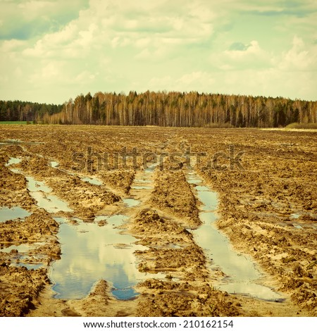 Mud on the field. Sky is reflected in a puddle. To a photo color toning is applied - stock photo