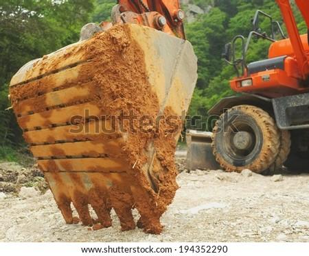 muddy backhoe digger scoop - stock photo