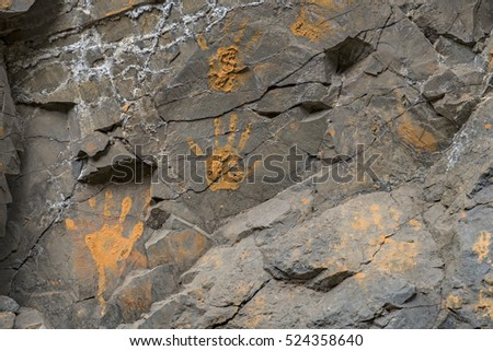 Muddy orange hand prints on a cracked stone wall