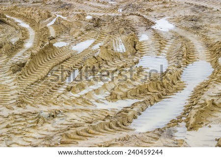 Muddy road with tire tracks and puddles, background. Selective focus.  - stock photo