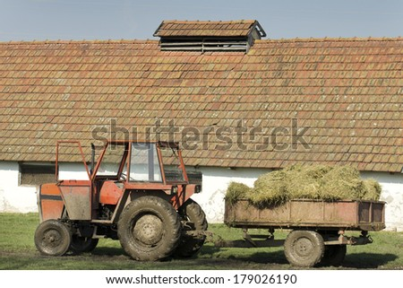 Muddy tractor with hay in trailer in front of stable - stock photo