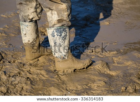 Muddy work boots, human leg with dirty rubber boots. Made with shallow dof.