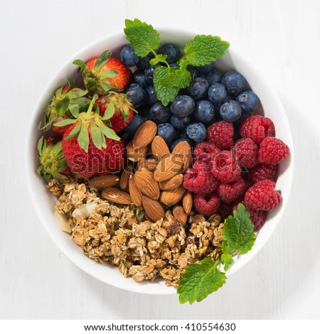 muesli, almonds and fresh berries in a bowl, top view, closeup - stock photo