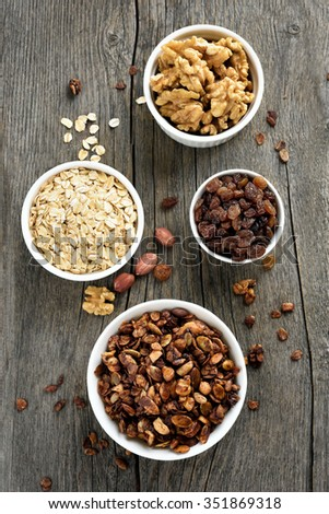 Muesli and ingredients on wooden background, top view - stock photo