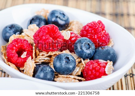 Muesli bowl for breakfast with blueberries and raspberries close up - stock photo