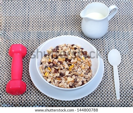 Muesli breakfast in transparent package.Spoon, dumbbell and milk - stock photo