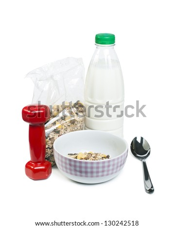 Muesli breakfast in transparent package.Spoon, dumbbell and milk white isolated - stock photo