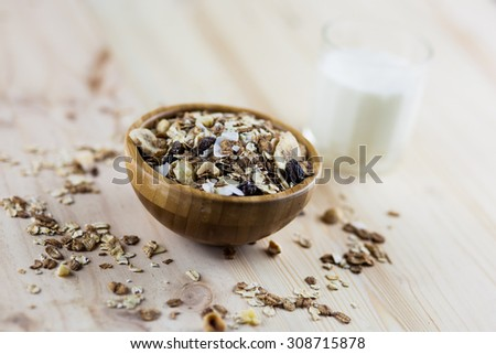 Muesli, granola and milk in blurred wooden background. (Shallow aperture intended for  the aesthetic quality of the blur.) - stock photo
