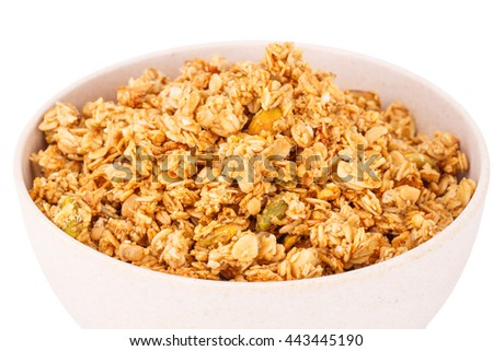 Muesli in bamboo bowl on white background.