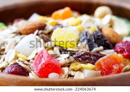 Muesli in bowl with nuts, berries, seeds, candied closeup - stock photo