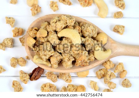 Muesli in wooden spoon on wooden table