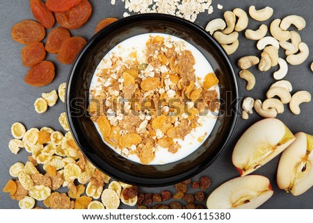 Muesli, nuts, fruits, milk and oatmeal for breakfast. Plate of oat flakes, cashew, apples and seeds for tasty breakfast on dark slate tray. Diet, Detox, Clean Eating or Vegetarian concept. - stock photo