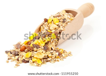 Muesli with dried fruits in wooden scoop isolated on white background
