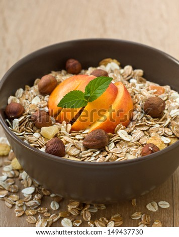 Muesli with fruit and nuts in a yellow bowl on wooden background