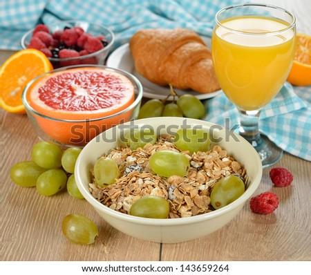 Muesli with grapes, orange juice and fresh fruit for breakfast - stock photo