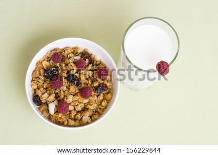 muesli with red raspberries in a bowl on a napkin with a glass of milk - stock photo
